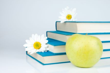 group of blue book, yellow apple and white flowers photo