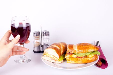 delicius sandwich on plate and a hand holding a glass of wine photo