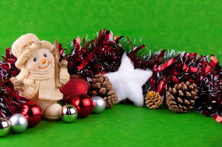 Christmas background - snowman, christmas balls and white snowstar on green background photo