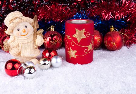 Candle, christmas balls and snowman on snow photo