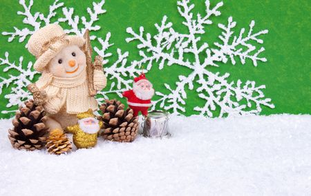 Snowman figure in snow  and two little santa clauses - christmas decoration photo
