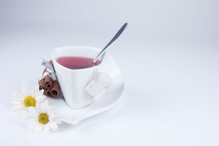 cup of tea with flowers and cinnamon with space for text photo