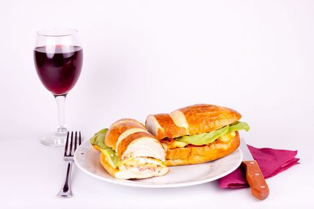 delicius sandwich with set for dining and a glass of wine photo