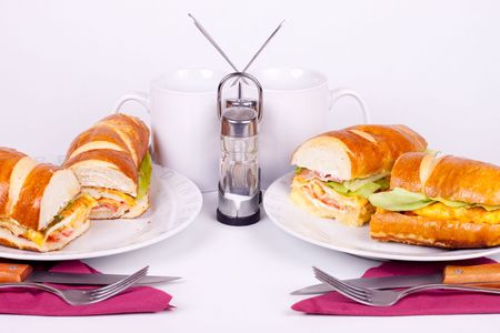 two delicius sandwiches with cups and set for dining photo