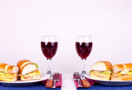 two delicious sandiches on plate with two glasses of wine  photo