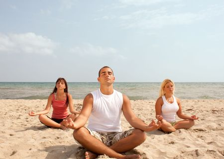 small group of young people meditating on the beach Stock Photo - 5976999