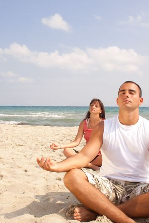two people relaxing, meditating on the beach photo