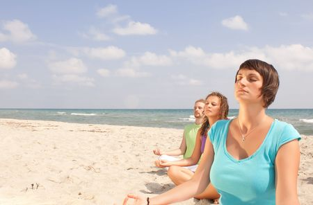three young people meditating on the beach photo