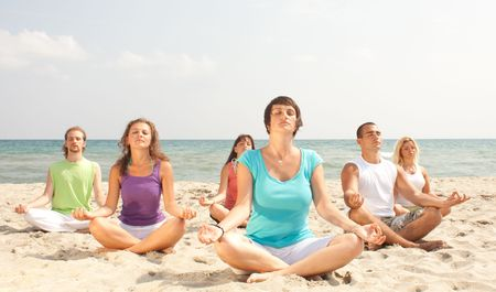 gruop of young people on the beach meditating photo