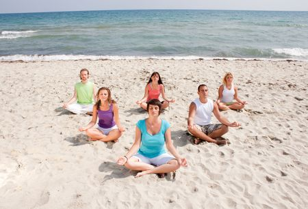 group of young people meditating on the beach photo