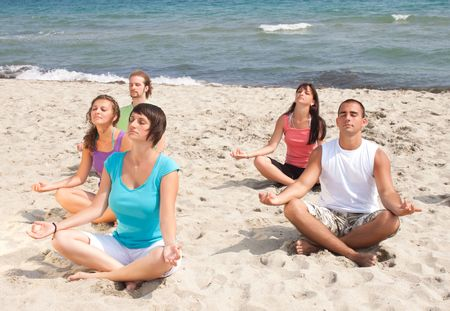 group of people meditating on the beach photo