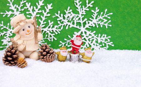 kiddish: Cute snowman figure in snow with three santa claus figures - christmas decoration Stock Photo
