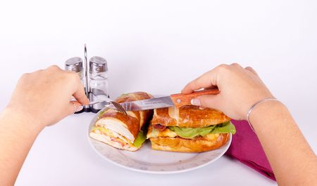 holding a knife and cutting a delicius sandwich  photo