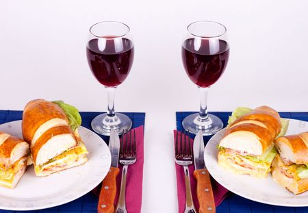 two delicious sandiches and glasses of wine photo