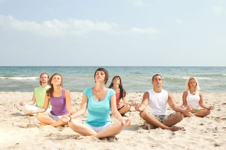group of young people meditating on the beach Stock Photo - 5998863