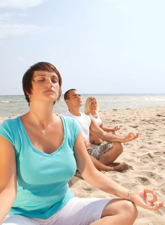 close up od meditating group of meditating people on the beach Stock Photo - 5998865
