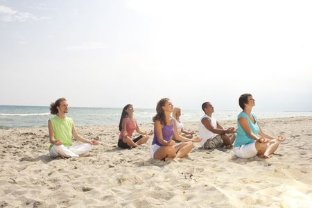 group of meditating people on the beach, left view photo