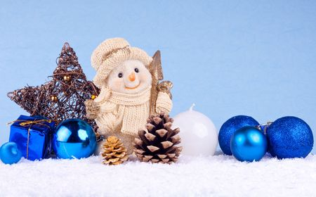 snowman with xmas balls, candle, oak ball and star on blue background photo