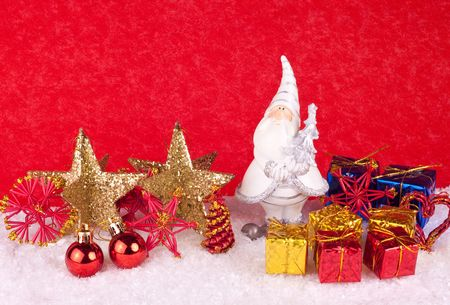 santa clause toy in snow on red background photo