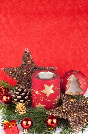 red christmas candles and xmas balls in snow on red background photo