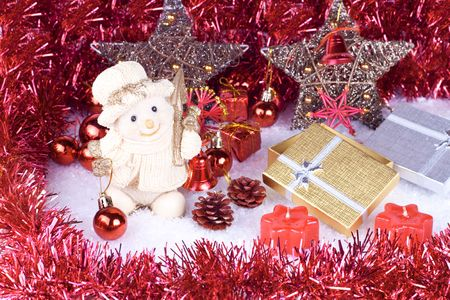 holding a christmas ornament: cute snowman figure on snow, xmas balls, candles and gifts Stock Photo