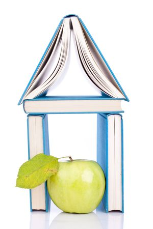 house from three blue books and green apple on white photo
