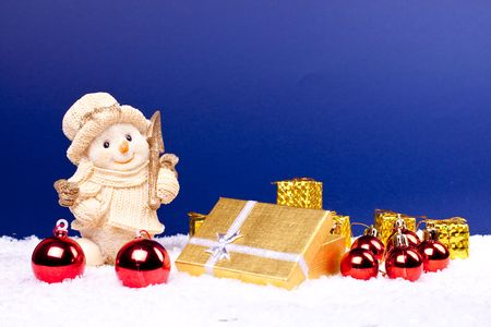 cute snowman figure on snow, xmas balls, candles and gifts photo