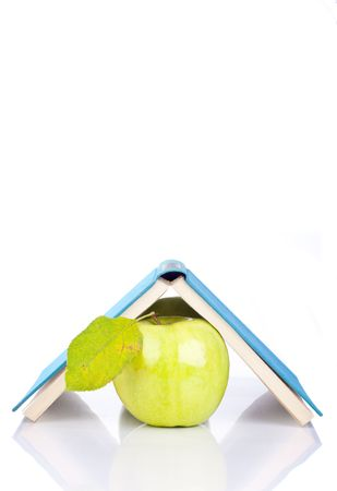 open blue book on green apple - isolated on white photo