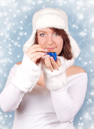 cute xmas girl opening a present - on a blue background snowflakes photo