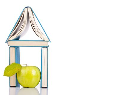 books standing like a house and green apple on white photo