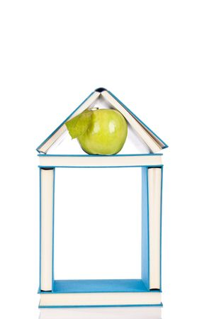 blue book house with green apple on white photo