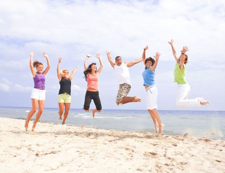Happy people jumping on the beach by the sea photo