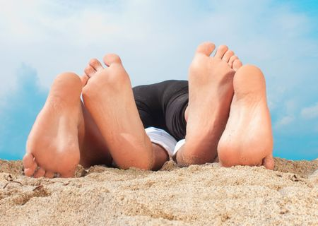coulpe lying on a sandy beach -  playing with feets photo