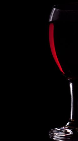 Half of glass of red wine on black background photo