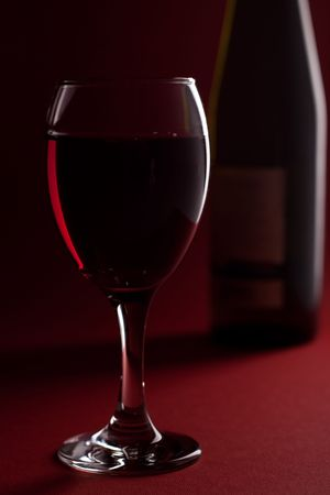 glass of red wine with bottle in background photo