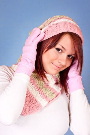 cute girl in scarf and cap on blue background photo