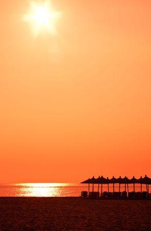 umbrellas on the beach with orange sky photo