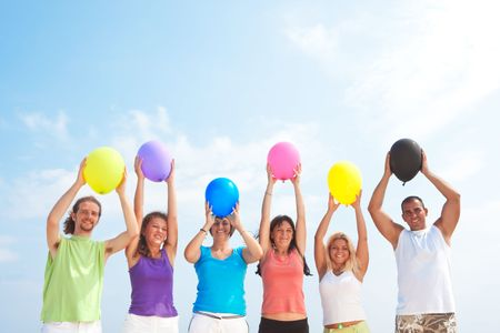 young people holding balloons in different colors photo