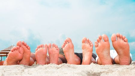 resting: Young couples feet at the  sandy beach Stock Photo