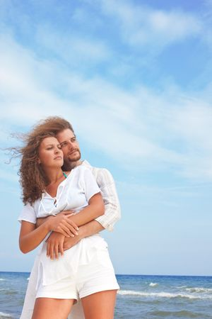 lovely couple standing by the blue sea photo