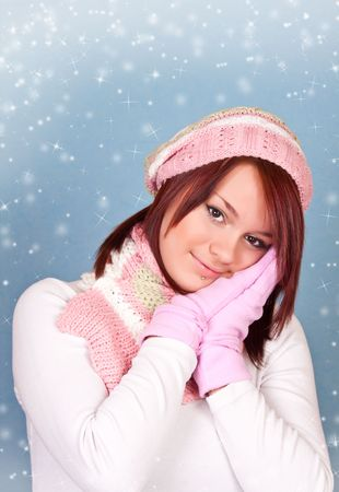 lovely girl in winter clothing on blue snowy background photo