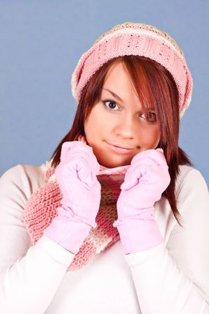 Cute young girl in winter clothing on blue background photo
