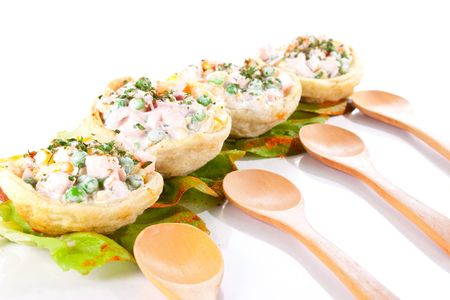 four russian salad in tortillas with wooden spoons photo