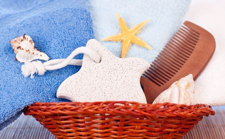 towels, foot stone, comb and shells in basket photo