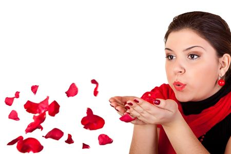 young woman blowing rose petals from her hands photo