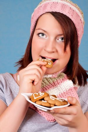 girl with hat and scarf eating a cookie photo