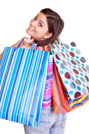 young happy brunette girl standing wearing jeans and holding colorful paper bags photo
