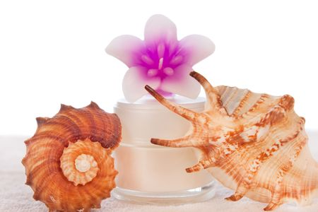 cream in white tube with pink flower decorated with seashells photo
