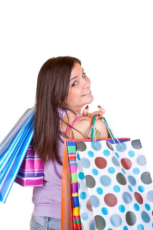 young happy brunette girl standing wearing jeans and holding colorful paper bags Stock Photo - 6540223