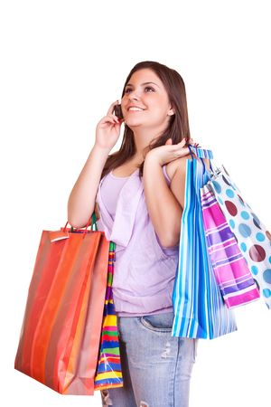 young happy brunette girl standing holding bags and talking on cell phone Stock Photo - 6540236
